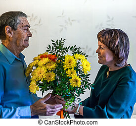 The girl gives flowers to an elderly man. Bouquet as a gift....