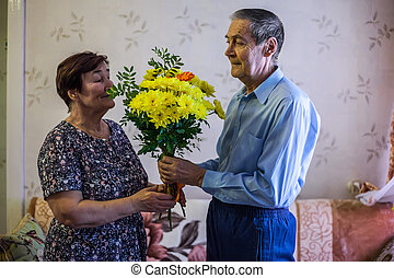 An elderly man gives flowers to his wife. Bouquet as a gift....