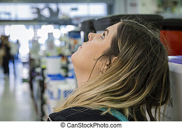 Woman looking up in a home furnishings retail store.