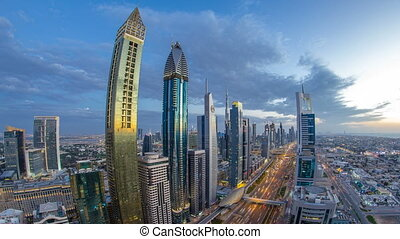 Scenic Dubai downtown architecture day to night timelapse. Top view over Sheikh Zayed road with illuminated skyscrapers and traffic.