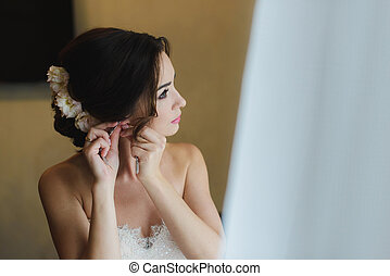 Bride in white wedding dress puts on earring. - Beautiful...