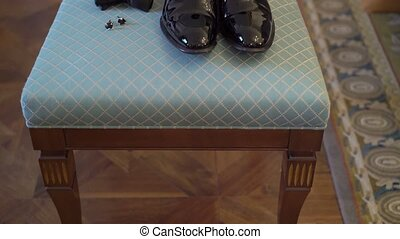 Man's black shoes, bowtie and cufflinks on a chair