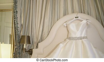 Beautiful wedding dress in bedroom on bed