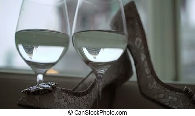 Woman's white shoes and two glasses of champagne near window...