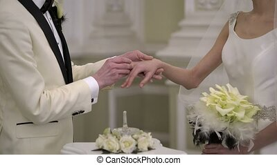 Groom puts on wedding ring on bride hand