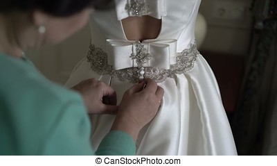 Woman buttoning wedding dress indoors