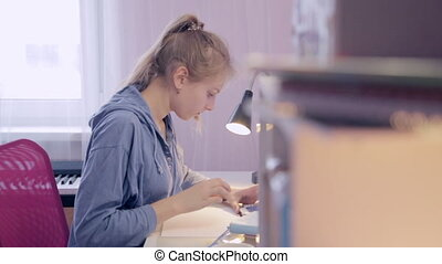 Teen Girl make homework using a smartphone - Teen Girl makes...