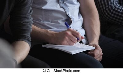 Man writing in notebook on lecture closeup