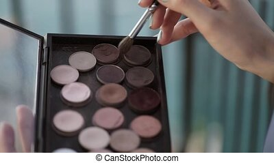 Makeup brush taking cosmetics from palette outdoors