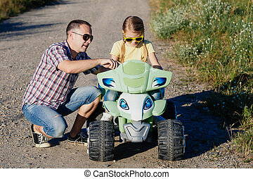 Father and daughter playing on the road at the day time....