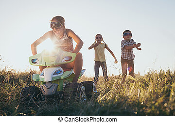 Happy little children playing on road at the sunset time.