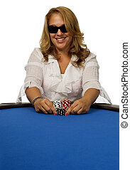 Woman pushes poker chips on blue table