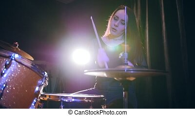 Dashing girl with flowing hair percussion drummer performing...