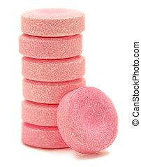 Pink antacid tablets - A pink antacid tablet, leans against...