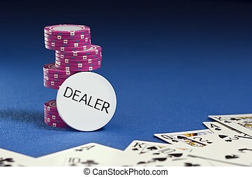 Dealer button with poker chips and playing cards on blue...