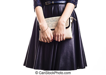 beautiful woman model in a leather skirt holds a handbag.