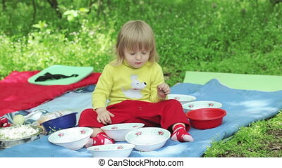 Serving picnic on nature - Girl child is served picnic table...