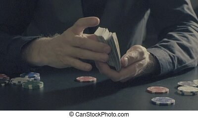 Poker game. Man's hands shuffing cards - Poker game -...