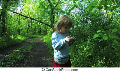 Girl child smelling leaves - In spring garden walks and girl...