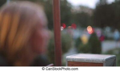 Side view of beautiful serious young woman sitting in a cafe. Close-up, blurred lights, urban street