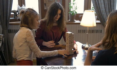 Young beautiful girl playing a board game. Together, they...