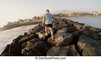 Back view of young man walking through the rocks on the beach. Man spending time outside near the sea in sunny day.