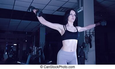 sports girl does exercises with dumbbells