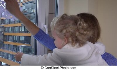woman with little girl stick paper snowflakes on window. mom with child have fun