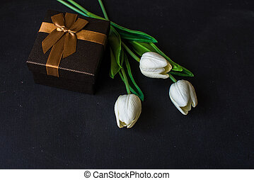 Holiday present concept - Tulips and git box on dark...