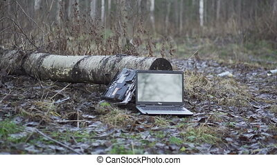 Smashing two laptops with shotgun in slow motion. Forest