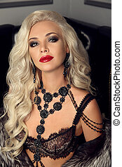 Beautiful fashion gorgeous woman portrait. Sexy elegant lady. Makeup, expensive jewelry set, blonde with long healthy wavy hair posing in elegant fur coat in modern interior.