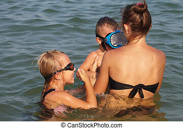 Mother with kids swimming in the sea