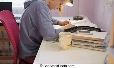 Teen girl doing her homework writing pen in a notebook