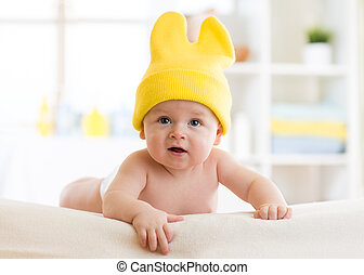 Baby with funny cap on head lying on bed in nursery