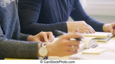 Close-up of two students studying at school library -...