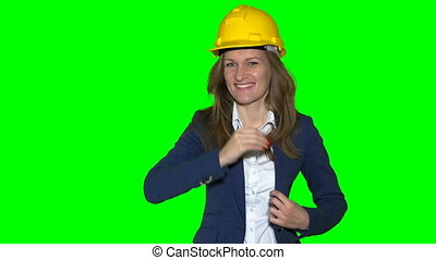 Happy realtor girl with yellow helmet on head and new house...
