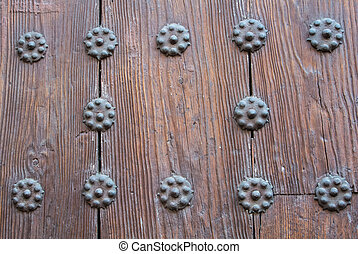 A close-up view to a part of old brown wooden door with metal rivets.