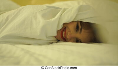 cheerful young girl with red lips in a white blanket on the bed