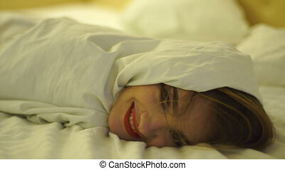 happy young girl with red lips in a white blanket on the bed...