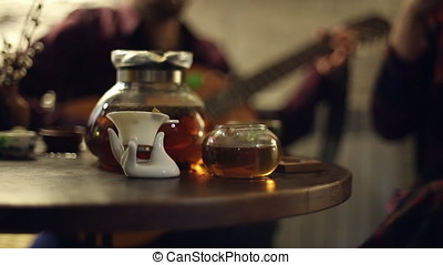 The musician plays the guitar, tea ceremony in the cafe