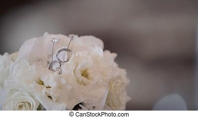 Pair of wedding rings on white flowers pillow closeup
