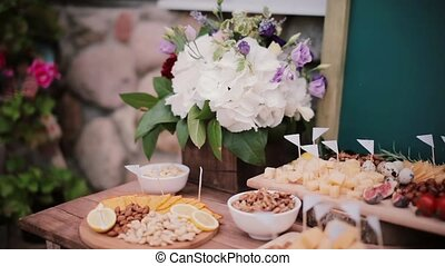 Cheese table with other snacks. Flowers, slices cheese,...