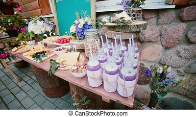 Cheese table with other snacks outside. Flowers, slices...