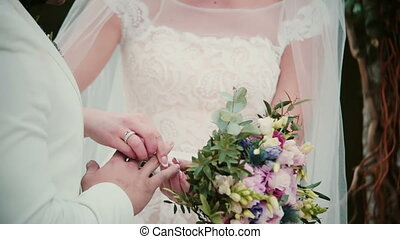 On a wedding day bride puts a golden ring on a groom finger....