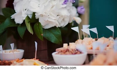 Close-up view to the cheese table. Flowers, slices cheese,...