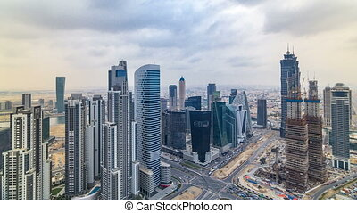 Dubai's business bay towers before sunset timelapse. Rooftop view of some skyscrapers and new towers under construction.