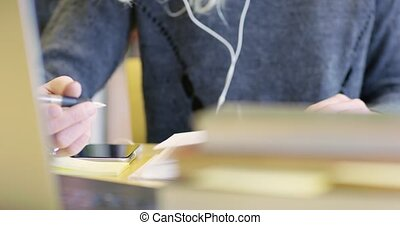 Close-up of a female student working at school library -...