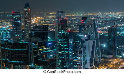 Dubai business bay towers illuminated at night timelapse. Rooftop view of some skyscrapers and new towers under construction.