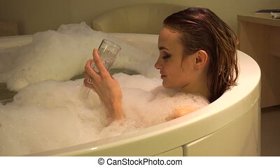 Gorgeous young woman bathing and relaxing with glass of...