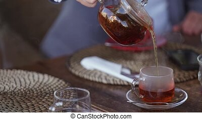 Man pouring tea in cup closeup